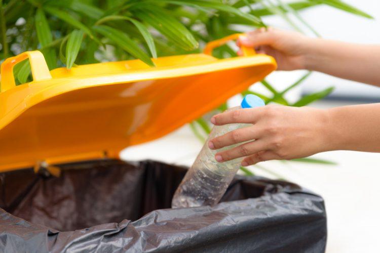Wegwerpen van plastic fles in afval container