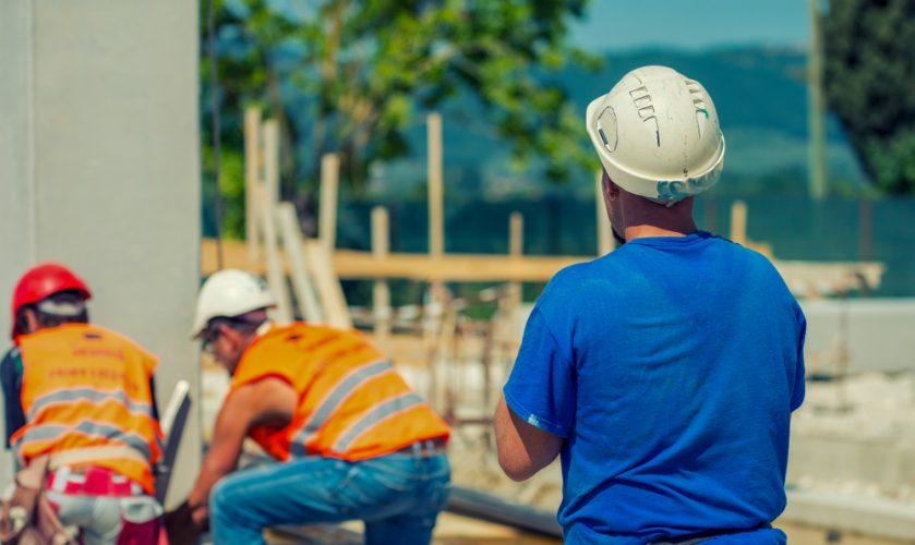Drie mannen aan het werk op de bouwplaats
